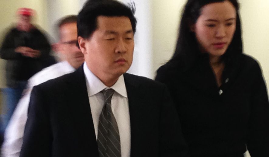 FILE - In this April 8, 2015 file photo, former New York City investment banker Jason Lee walks with his wife Alicia into Suffolk County Court in Riverhead, N.Y., where  Lee faces charges he raped a woman from Ireland that he took home after celebrating his birthday at a Hamptons nightclub. Closing arguments are scheduled in the trial of Lee who has pleaded not guilty and his defense attorney has argued the sex was consensual. (AP Photo/Frank Eltman, File)