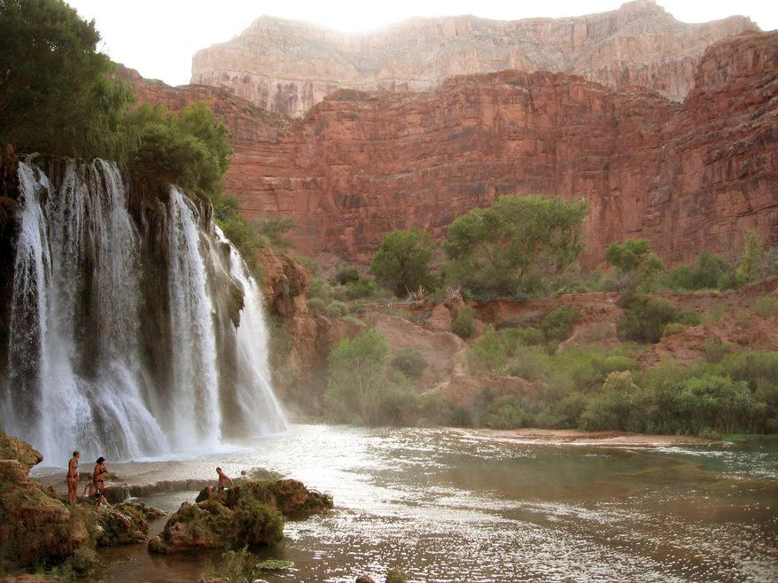 This Sept. 26, 2014 photo shows hikes enjoying Upper and Lower Navajo Falls, the first waterfalls on a grueling three-day hike in Havasu Canyon in northern Arizona. The trip offers bliss by way of blisters. (Giovanna Dell'Orto via AP)