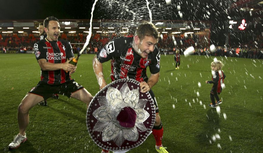 In this image taken Monday April 27, 2015, Bournemouth's Ryan Fraser, right, is sprayed with champagne by teammate Marc Pugh after the final whistle their victory over  Bolton  in  their English Championship soccer match at Dean Court, Bournemouth, England. Bournemouth won the match 3-0 which almost certainly means they will be promoted to the English Premier League next season for the first time in the club's history.  (John Walton/PA via AP)  UNITED KINGDOM OUT