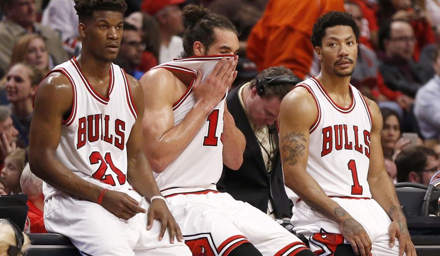 Chicago Bulls' players from left, Jimmy Butler, Joakim Noah, and Derrick Rose, wait for play to resume during the second half in Game 5 of the NBA basketball playoffs against the Milwaukee Bucks Monday, April 27, 2015, in Chicago. The Bucks won 94-88. (AP Photo/Charles Rex Arbogast)