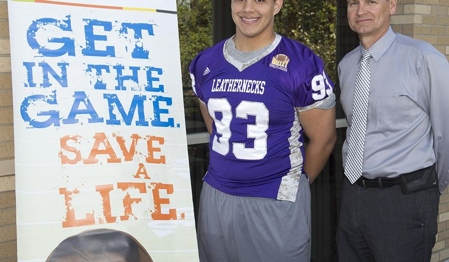 This April 23, 2015 photo provided by the Western Illinois University Visual Production Center shows 20-year-old sophomore Jordan Veloz, a linebacker for the school's football team, posing with head coach coach Bob Nielson next to a poster for the Be The Match marrow registry in Macomb, Ill. Veloz is set to become a most valuable player for an infant with a rare immune disorder. The school said Monday, April 27, 2015, that Veloz signed up last year during a bone marrow registry drive on campus. He was informed last month that he might be a match and then this month he was told that he was a match. (Larry Dean/Western Illinois University Visual Production Center via AP)
