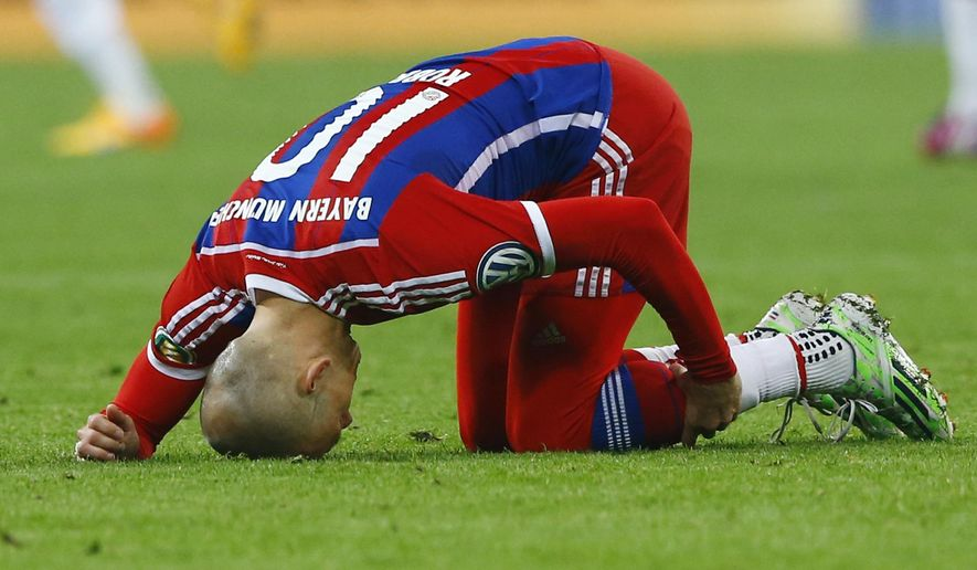 Bayern's Arjen Robben holds his leg during the German soccer cup (DFB Pokal) semifinal match between FC Bayern Munich and Borussia Dortmund at the Allianz Arena in Munich, Germany, on Tuesday, April 28, 2015. (AP Photo/Matthias Schrader)