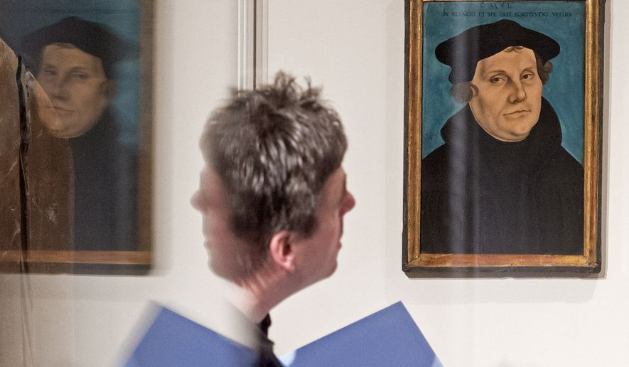 A visitor is reflected in a showcase besides the painting 'Bildnis Martin Luthers' (1529) by Lucas Cranach the Elder during the press preview at the exhibition 'The Luther Portraits of the Cranach Workshop' at the Wartburg castle in Eisenach, Germany, Tuesday, March 31, 2015. The exhibition, that also shows Luther portraits of contemporary artists, starts on April 2 and lasts until July 19, 2015. (AP Photo/Jens Meyer)