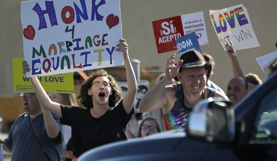 Same-sex marriage supporters hold signs encouraging drivers to honk in support of marriage equality during a rally Tuesday, April 28, 2015, in Salt Lake City. Supporters and opponents of same-sex marriage rallied in Utah on Tuesday after the U.S. Supreme Court heard arguments on the constitutionality of laws banning such marriages. Opponents of gay marriage will hold a rally at Utah's state Capitol Tuesday night. (AP Photo/Rick Bowmer)
