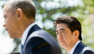 Japanese Prime Minister Shinzo Abe listens as President Barack Obama speaks during their joint news conference in the Rose Garden of the White House in Washington, Tuesday, April 28, 2015. (AP Photo/Andrew Harnik)