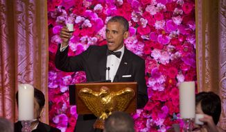 President Barack Obama raise a cup of sake as he offers a toast as he and first lady Michelle Obama host Japanese Prime Minister Shinzo Abe and his wife Akie Abe at the State Dinner at the White House in Washington, Tuesday, April 28, 2015. (AP Photo/Pablo Martinez Monsivais)