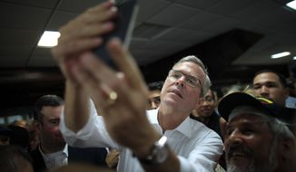 Former Florida Gov. Jeb Bush takes a selfie with a supporter's phone after holding a town hall meeting with Puerto Rico's Republican Party in Bayamon, Puerto Rico, Tuesday, April 28, 2015. The 2016 GOP presidential prospect delivered a speech on economic opportunities peppered with Spanish. He's fluent in the language, and often uses it in Florida, but it's rarely heard in Republican presidential campaign politics. (AP Photo/Ricardo Arduengo)