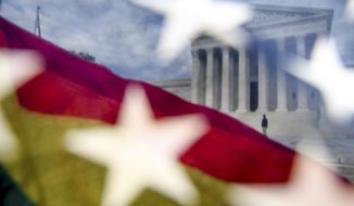 A rainbow colored flag, seen through an American flag, flies in front of the Supreme Court in Washington, Monday, April 27, 2015, as the Supreme Court is set to hear historic arguments in cases that could make same-sex marriage the law of the land. . (AP Photo/Andrew Harnik)