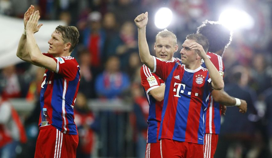 Bayern's Bastian Schweinsteiger, left, and Philipp Lahm celebrate after the German first division Bundesliga soccer match between FC Bayern Munich and Hertha BSC at the Allianz Arena in Munich, Germany, on Saturday, April 25, 2015. (AP Photo/Matthias Schrader)