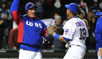 Chicago Cubs shortstop Starlin Castro, right and manager Joe Maddon (70) left, celebrate their win against the Pittsburgh Pirates in a baseball game, Tuesday, April 28, 2015 in Chicago.  The Cubs won 6-2. (AP Photo/David Banks)