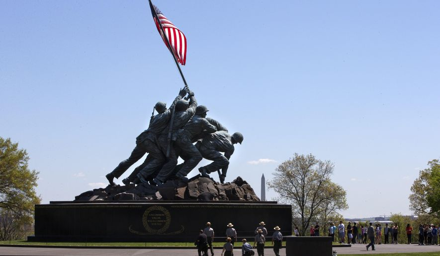 National Park Service rangers walk toward the U.S. Marine Corps War Memorial in Arlington, Va., Wednesday, April 29, 2015. The famous bronze U.S. Marine Corps War Memorial overlooking Washington that depicts Marines raising the American flag at Iwo Jima during World War II has begun turning green with age but now will be restored with a $5.37 million gift. Philanthropist David Rubenstein announced Wednesday that he will give the National Park Foundation the funds needed to wash, wax and restore the memorial and its plaza and landscaping. Improvements are also planned for the memorial's signage and access for handicapped visitors. The project will also restore the memorial's engravings to be much brighter. (AP Photo/Jacquelyn Martin)