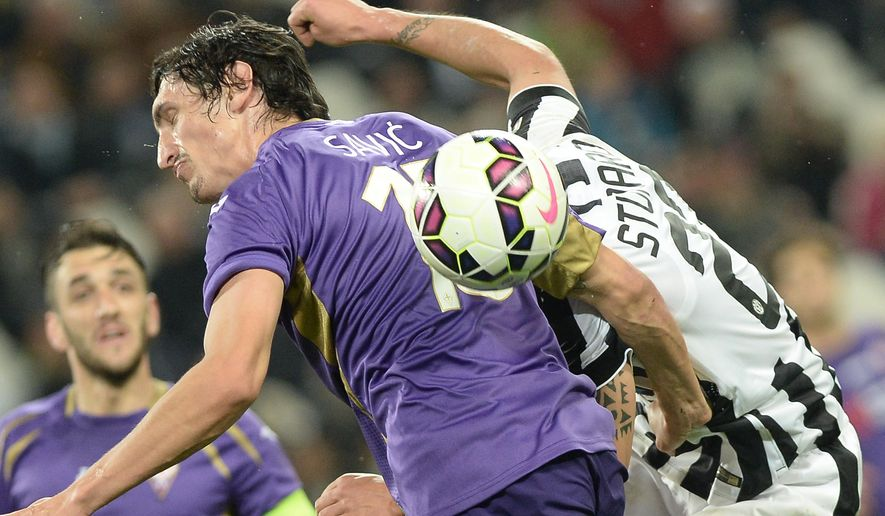Juventus' Stefano Sturaro, right, challenges for the ball with Fiorentina's Stefan Savic during a Serie A soccer match between Juventus and Fiorentina at the Juventus stadium, in Turin, Italy, Wednesday, April 29, 2015. (AP Photo/Massimo Pinca)