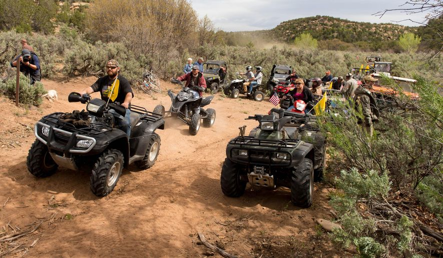 FILE - This May 10, 2014, file photo, ATV riders cross into a restricted area of Recapture Canyon, north of Blanding, Utah, in a protest against what demonstrators call the federal government's overreaching control of public lands. A southern Utah county commissioner and three others on trial in federal court crossed the line when they knowingly broke the law during an ATV protest ride last year through a canyon home to Native American cliff dwellings, prosecutors said Wednesday, April 29, 2015. (Trent Nelson/The Salt Lake Tribune via AP, File)
