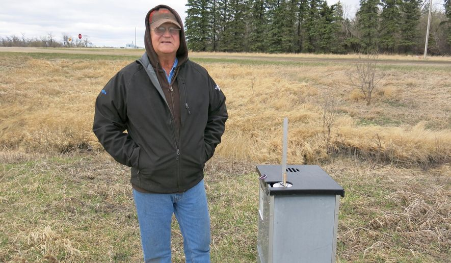 Gerry Zimmerman stands near a drain tile control structure on his farm near Moorhead, Minn., on April 21, 2015.  Zimmerman is experimenting with sub irrigation, pumping water back into the underground drain tile during dry conditions.  (Dan Gunderson /Minnesota Public Radio via AP)