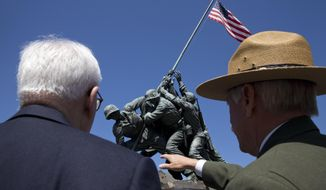 Jonathan Jarvis, director of the National Park Service,  right, points out some items that are planned for improvement at the U.S. Marine Corps War Memorial, in Arlington, Va., Wednesday, April 29, 2015, with David Rubenstein, left, a businessman and philanthropist whose gift of $5.37 million will go toward a newly announced restoration project at the memorial, the sculpture of which was inspired by the U.S. battle at Iwo Jima. The famous bronze U.S. Marine Corps War Memorial overlooking Washington that depicts Marines raising the American flag at Iwo Jima during World War II has begun turning green with age but now will be restored with a $5.37 million gift. Philanthropist David Rubenstein announced Wednesday that he will give the National Park Foundation the funds needed to wash, wax and restore the memorial and its plaza and landscaping. Improvements are also planned for the memorial's signage and access for handicapped visitors. The project will also restore the memorial's engravings to be much brighter. (AP Photo/Jacquelyn Martin)