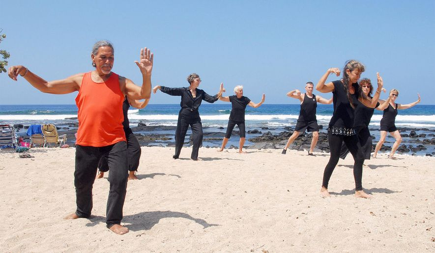 In this April 25, 2015 photo, beginners partake in the annual World Tai Chi Qigong Day in Kona, Hawaii.  Around West Hawaii, tai chi stays pretty well under the radar. Lacking the high profile brick-and-mortar schools of the mainland, instructors here of the ancient martial art tend to pass on their knowledge in civic centers, parks, open areas and other temporary facilities. (Laura Shimabuku/West Hawaii Today via AP)