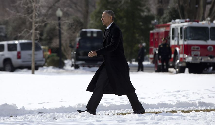 President Obama walks on a path across the snow covered South Lawn of the White House to board Marine One in Washington, for the short trip to Andrews Air Force Base, en route to Chicago, on Feb. 19, 2015. (Associated Press) **FILE**