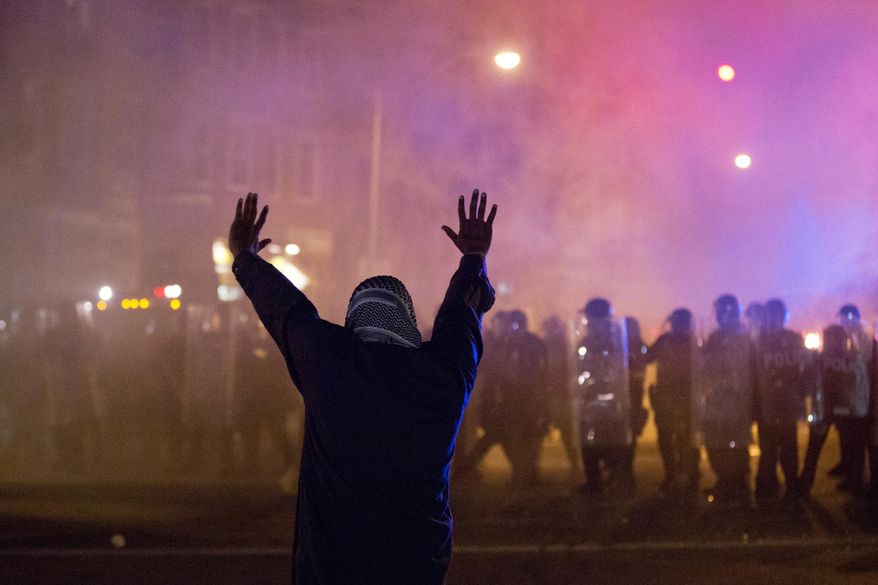 A protestor faces police enforcing a curfew Tuesday night in Baltimore. A line of police behind riot shields hurled smoke grenades and fired pepper balls at dozens of protesters to enforce a citywide curfew. (Associated Press)