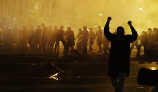 Police in riot gear advance on the crowd after a 10 p.m. curfew went into effect Tuesday in Baltimore. (Associated Press)