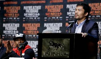 Floyd Mayweather Jr., left, listens as  and Manny Pacquiao talks during a pre-fight news conference in Las Vegas, Wednesday, April 29, 2015. Floyd Mayweather Jr. and Manny Pacquiao are scheduled to fight May 2. (AP Photo/Chris Carlson)