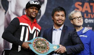 Boxers Floyd Mayweather Jr., left, and Manny Pacquiao pose with a WBC belt during a press conference Wednesday, April 29, 2015, in Las Vegas. Mayweather will face Pacquiao in a welterweight title fight in Las Vegas on May 2. At right is Freddie Roach, Pacquiao's trainer. (AP Photo/John Locher)