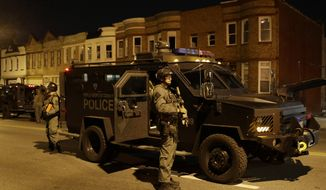 Prince George's County Police enforce curfew, Tuesday, April 28, 2015, in Baltimore, a day after unrest that occurred following Freddie Gray's funeral. (AP Photo/Patrick Semansky)