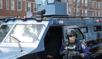 An Anne Arundel County policeman guards the intersection of North Avenue and Pennsylvania Avenue, Wednesday, April 29, 2015, in Baltimore. Schools reopened across the city and tensions seemed to ease Wednesday after Baltimore made it through the first night of its curfew without the widespread violence many had feared. People in Baltimore have been angry over the police-custody death of Freddie Gray. (AP Photo/Patrick Semansky)
