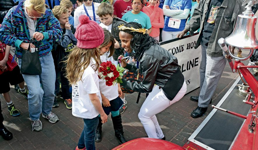 Caroline Rotich, right, the 2015 winner of the Boston Marathon, signs autographs during the parade to honor Rotich that was held on the Santa Fe, New Mexico Plaza on Monday, April 27, 2015. (Clyde Mueller/Santa Fe New Mexican via AP)