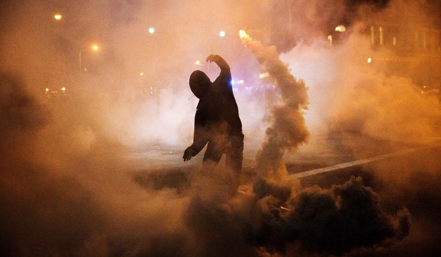 A protester throws a tear gas canister back toward riot police after a 10 p.m. curfew went into effect in the wake of Monday's riots following the funeral for Freddie Gray, Tuesday, April 28, 2015, in Baltimore. (AP Photo/David Goldman)