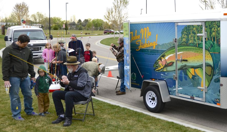 ADVANCE FOR THE WEEKEND OF MAY 2-3 AND THEREAFTER - Anglers gear up with fishing tackle at the Idaho Fish and Game trailer in Meridian, Idaho, April 11, 2015. The trailer travels to local fishing spots in Southwest Idaho, provides a persons' needs for a day of fishing for free and as long as people sign up at the trailer before fishing, no license is required. (Roger Phillips/The Idaho Statesman via AP)