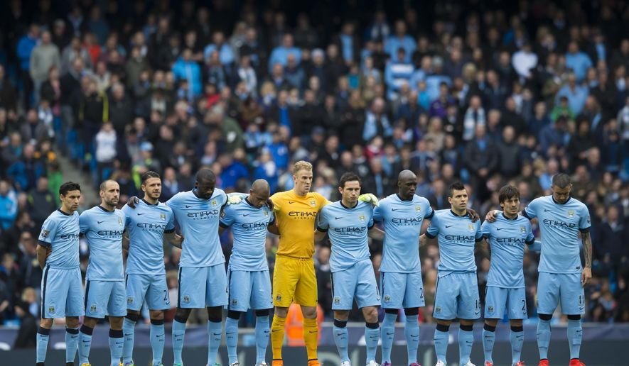 Manchester City players line up for a minutes silence to remember the victims of the Bradford fire before the English Premier League soccer match between Manchester City and Aston Villa at the Etihad Stadium, Manchester, England, Saturday April 25, 2015. (AP Photo/Jon Super)