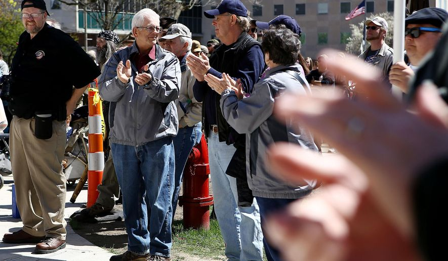 Gun owners and supporters listen to state Rep. speak Gary Glenn during an open carry gun rally and march Wednesday, April 29, 2015,  in downtown Lansing, Mich. (Danielle Duval/The Jackson Citizen Patriot via AP) ALL LOCAL TELEVISION OUT; LOCAL TELEVISION INTERNET OUT