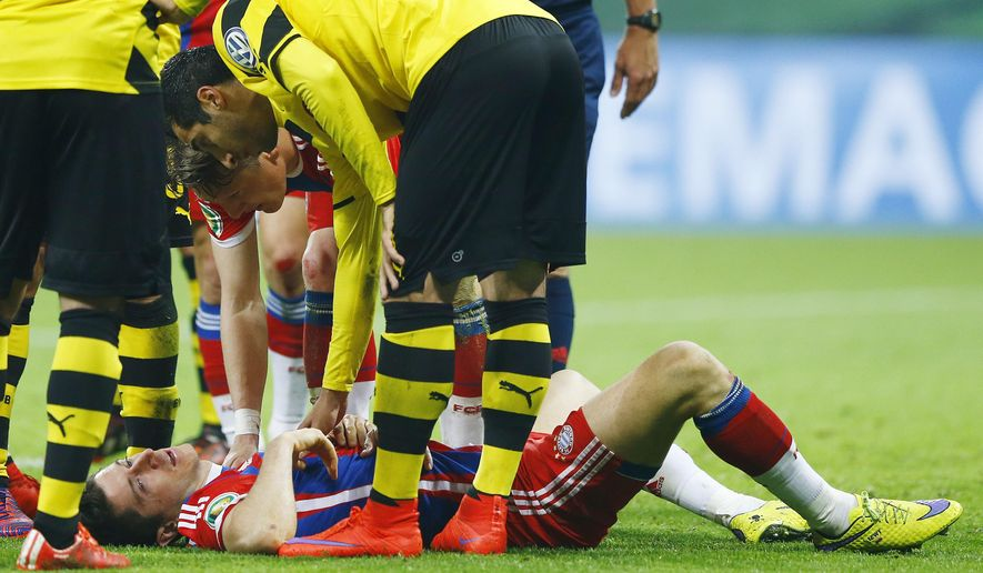 Bayern's Robert Lewandowski lies injured on the pitch during the German soccer cup (DFB Pokal) semifinal match between FC Bayern Munich and Borussia Dortmund at the Allianz Arena in Munich, Germany, on Tuesday, April 28, 2015. (AP Photo/Matthias Schrader)