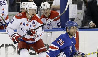 Washington Capitals center Nicklas Backstrom (19) and New York Rangers right wing Martin St. Louis (26) look down ice after a pass during the first period of Game 1 in the second round of the NHL Stanley Cup hockey playoffs, Thursday, April 30, 2015, in New York. (AP Photo/Frank Franklin II)