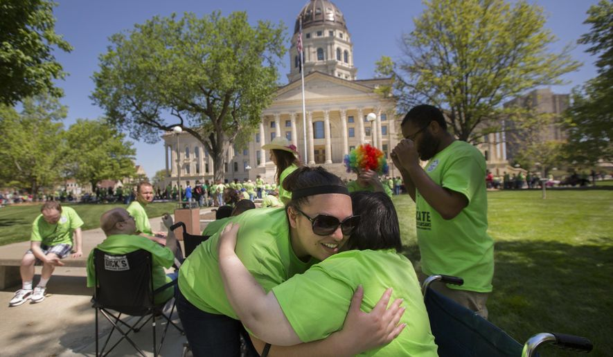 Lawrence resident Rachel Blann, right, gives a hug to her facilitator, Roxana Covarrubias, during a rally for those protesting against potential cuts to disability services, Thursday, April 30, 2015, on the south side of the Kansas Statehouse in Topeka, Kan. Several hundred Kansans with disabilities and advocates for disability services came to the Capitol to speak with lawmakers, who are in the middle of attempting to balance the state budget. (Nick Krug/The Lawrence Journal-World via AP)