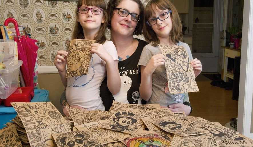 ADVANCED FOR RELEASE SATURDAY, MAY 2, 2015 Freelance artist Melissa Shimek, 44, center, poses with her eight-year-old twin daughters Ginny Shimek, left, and Mary Shimek, right, on April 13, 2015 in their home in Millcreek Township, near Erie, Pa. Shown are dozens of illustrated paper bags Melissa has made for their school lunches every day for over two years. The bag collection will be on display as part of a back-to-school-themed show at Blasco Library in Erie beginning in August, 2015. (Andy Colwell/Erie Times-News via AP)