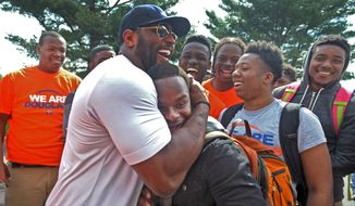 Former Baltimore Ravens NFL football player Ray Lewis hugs 17-year-old Azariah Bratton-Bey Jr., a senior running back on Frederick Douglass High's football team, during a visit to the school Thursday, April 30, 2015, in Baltimore. Lewis, Ravens coach John Harbaugh, and other players visited schools in downtown Baltimore in the aftermath of riots that ravaged the city. (Kenneth K. Lam/Baltimore Sun via AP) THE WASHINGTON EXAMINER OUT
