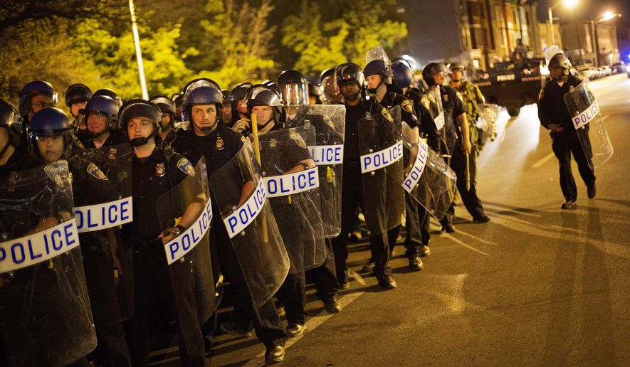 Police in riot gear line up near the scene of riots ahead of a 10 p.m. curfew Wednesday, April 29, 2015, in Baltimore. The curfew was imposed after unrest in Baltimore over the death of Freddie Gray while in police custody. (AP Photo/David Goldman)