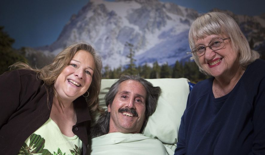 In this photo taken Wednesday, April 22, 2015, Greg Chambers smiles and poses with his girlfriend Connie Wolfe, left, and his mother, Susan Chambers, in his Mishawaka, Ind.,  home. Chambers, who was paralyzed in a March 1982 accident at age 16, will be turning 50 this month. (Greg Swiercz/South Bend Tribune via AP)