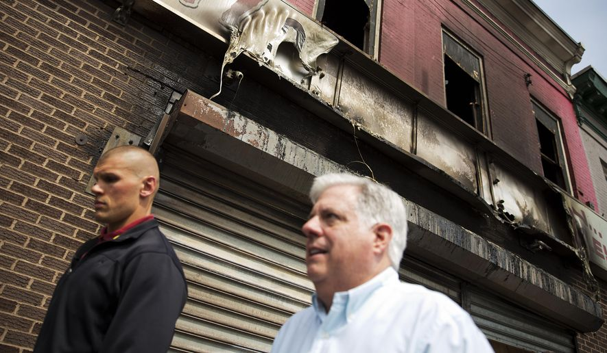 Maryland Gov. Larry Hogan, right, walks past a burned out shoe store while visiting local businesses, Thursday, April 30, 2015, in Baltimore, that were damaged in the rioting following Monday's funeral for Freddie Gray, who died in police custody. (AP Photo/David Goldman)