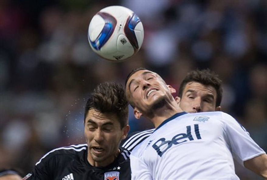 D.C. United's Michael Farfan, left, and Vancouver Whitecaps' Russell Teibert vie for the ball during the first half of an MLS soccer game Saturday, April 25, 2015, in Vancouver, British Columbia. (Darryl Dyck/The Canadian Press via AP)