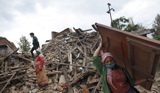 Nepalese earthquake-affected victims salvage belongings from their damaged homes in Lalitpur, on the outskirts of Kathmandu, Nepal, Thursday, April 30, 2015. (AP Photo/Niranjan Shrestha)