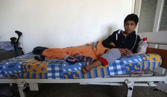 In this picture taken on Friday, April 17, 2015, 16-year-old Anas Baroudi shows his missing left foot, lost almost three years ago in the civil war in Syria, on his bed at the Dar Al-Salameh center for recovery and physiotherapy, in Kilis town near the Syrian border in Turkey. (AP Photo/Hussein Malla)