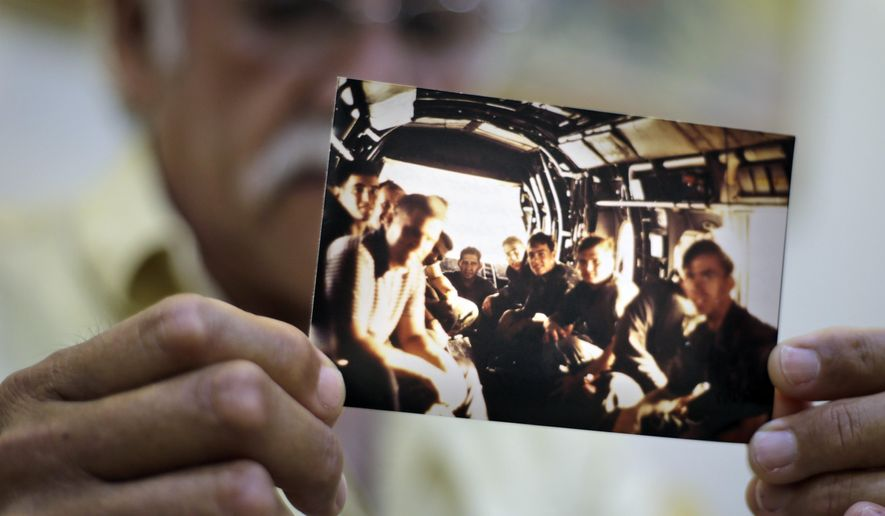 In this Tuesday, April 28, 2015 photo, former U.S. Marines Master Gunnery Sgt. Juan Valdez of Oceanside, California, holds a photo of himself, rear center, sitting on the last helicopter leaving the U.S. Embassy in Saigon on April 30, 1975, in Ho Chi Minh City, Vietnam. On the 40th anniversary of the fall of Saigon, 13 Marines  returned to dedicate a plaque to their two fallen brothers at the site of the old embassy, which is now the U.S. Consulate. (AP Photo/Dita Alangkara)