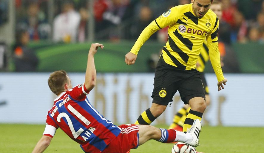 Bayern's Philipp Lahm, left, and Dortmund's Ilkay Gundogan challenge for the ball during the German soccer cup (DFB Pokal) semifinal match between FC Bayern Munich and Borussia Dortmund at the Allianz Arena in Munich, Germany, on Tuesday, April 28, 2015. (AP Photo/Matthias Schrader)