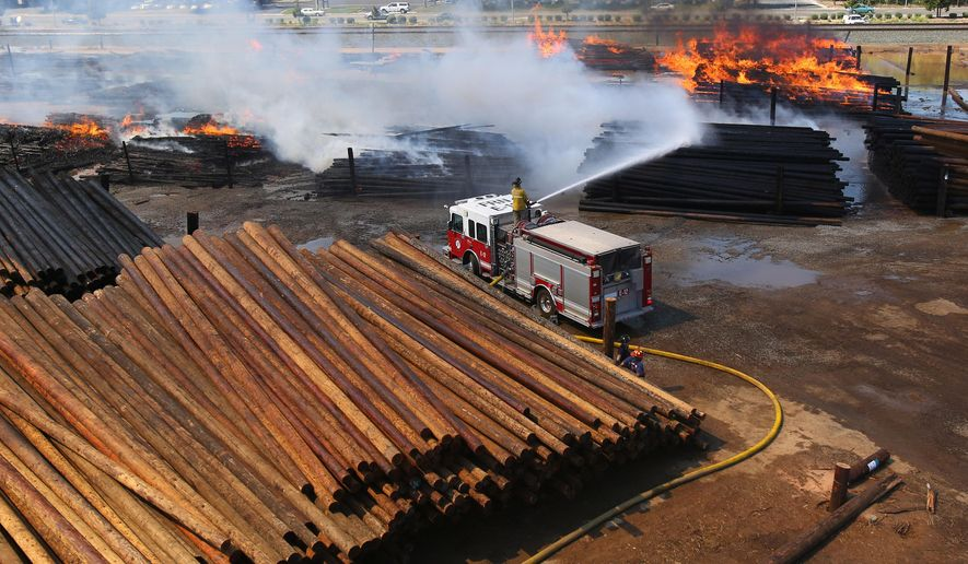 Fresno firefighter Dustin Richards sprays water on a large scale fire at the McFarland Cascade utility yard  Thursday, April 30, 2015 in Fresno, Calif. Between 400 and 1,000 wooden power poles owned by Pacific Gas and Electric on the two-acre yard are either burned or threatened, Fresno Fire Department spokesman Pete Martinez said. Damage is estimated at $1.3 million, and its cause is under investigation, he said. (AP Photo/Gary Kazanjian)