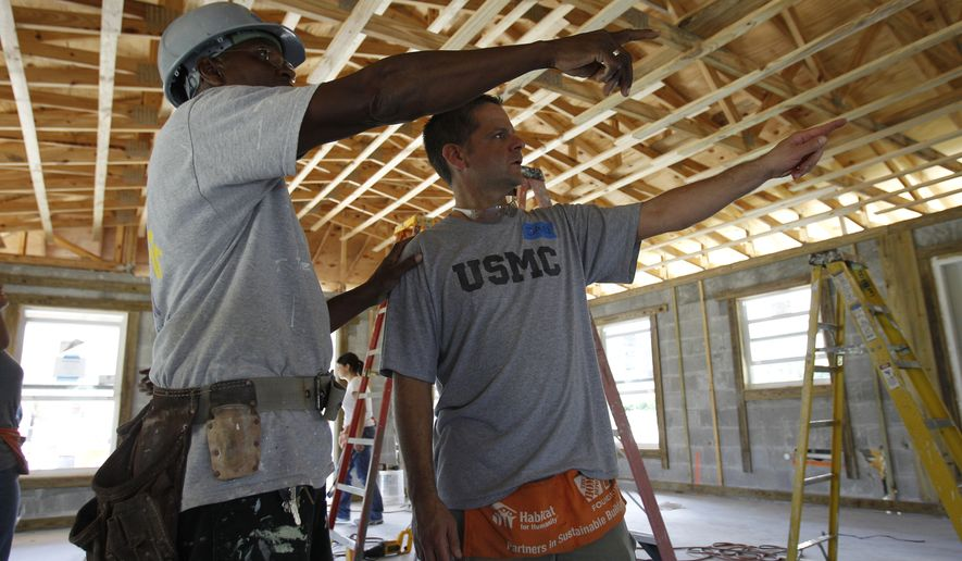 Gavin Canady (left) of Habitat for Humanity works with former U.S. Marine Dan Caporale of Fort Lauderdale, Florida, in building a Habitat for Humanity home in Miami. (Associated Press)
