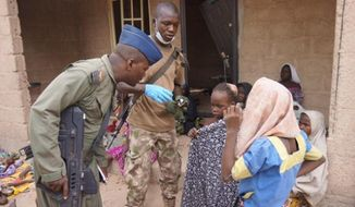 In this photo made available by the Nigerian Military taken Wednesday, April 29, 2015, a Nigerian soldier speaks to woman and children that were allegedly rescued by the Nigerian Military after being taken by Islamic extremists in Sambisa Forest, Nigeria. Scores more women and children have been rescued from Islamic extremists in the remote Sambisa Forest, Nigeria's military said amid reports that some of the women fought their rescuers fiercely. (Nigerian Military via AP)