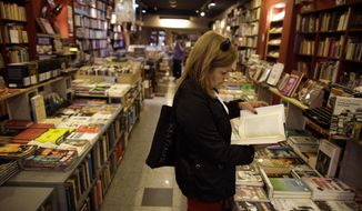 In this Tuesday, April 21, 2015, file photo, a customer reads a book at a bookstore in Buenos Aires, Argentina. (AP Photo/Victor R. Caivano, File)
