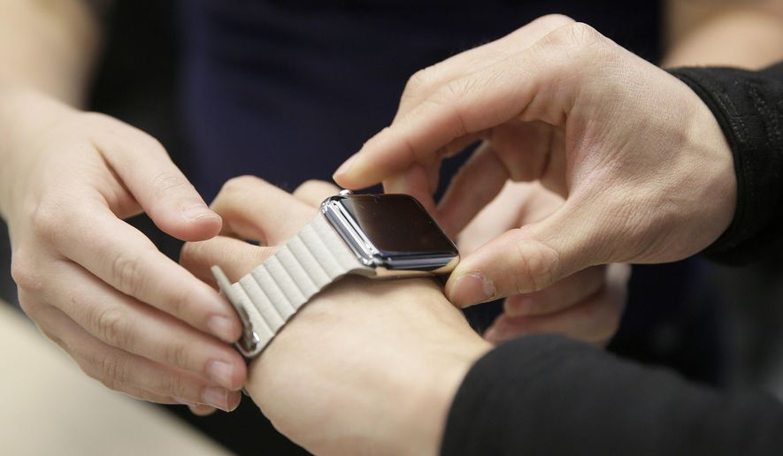 FILE - In this Friday, April 10, 2015, file photo, a customer tries on Apple's new watch at a store in San Francisco. The Apple Watch's heart rate monitor might not work if there is a tattoo on the wearer's wrist. (AP Photo/Eric Risberg, File)